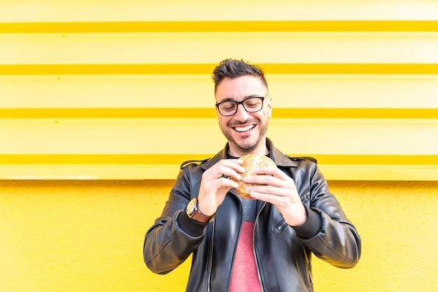 Homem latino comendo um hambúrguer ao ar livre
