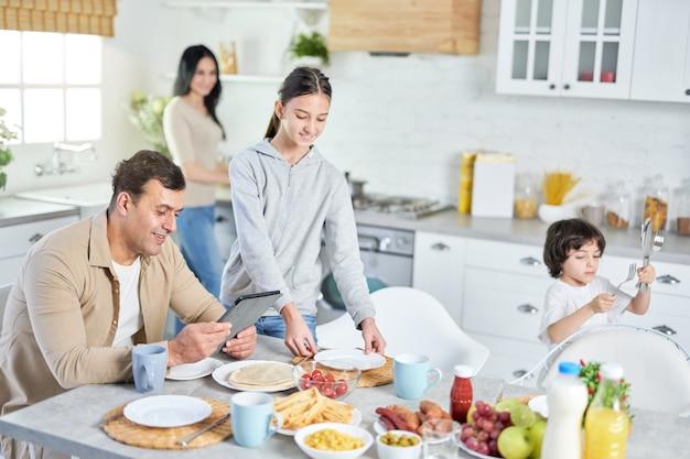 Homem latino de meia idade usando o tablet pc, esperando o jantar, enquanto seus filhos felizes e a esposa servindo a mesa na cozinha em casa. foco seletivo