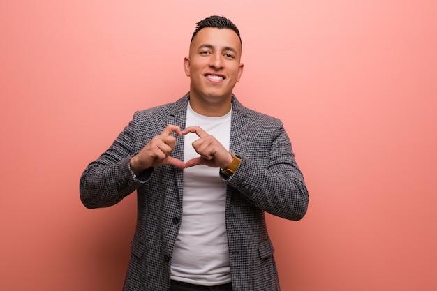 Homem latino elegante jovem, fazendo uma forma de coração com as mãos
