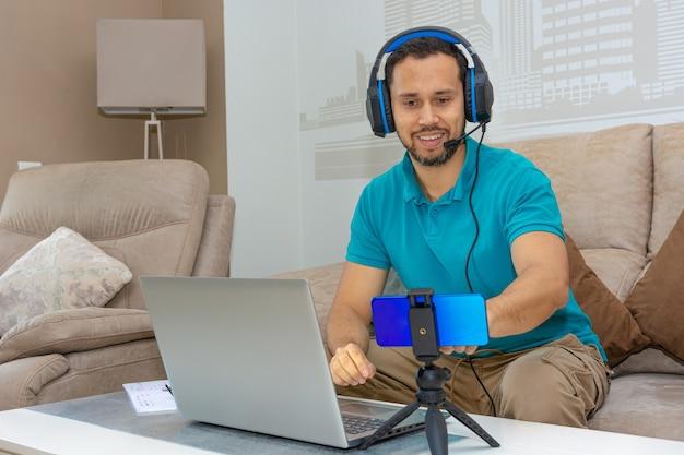 Homem latino fazendo um curso online no sofá de sua casa (conceito de curso online e ensino superior)