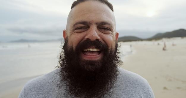 Homem latino feliz com barba grande na praia, olhando para a câmera e sorrindo.