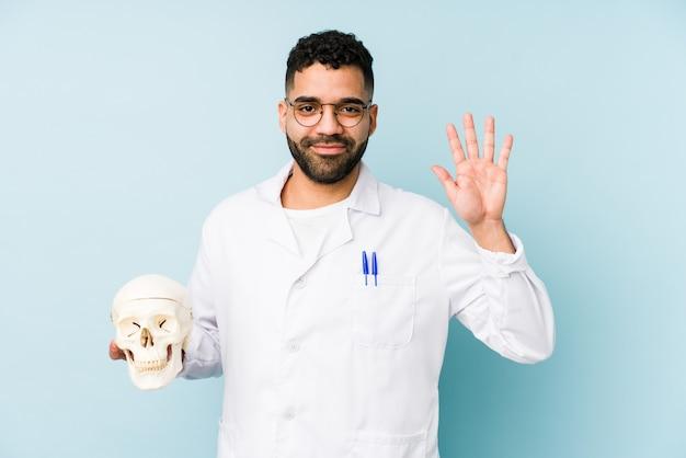 Homem latino jovem médico segurando um crânio sorrindo alegre mostrando o número cinco com os dedos.