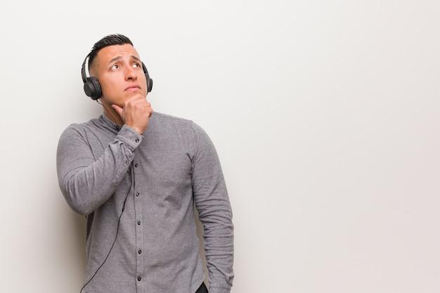 Homem latino jovem ouvindo música duvidando e confuso