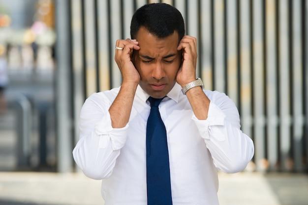 Homem latino latente forçado segurando a cabeça com as mãos