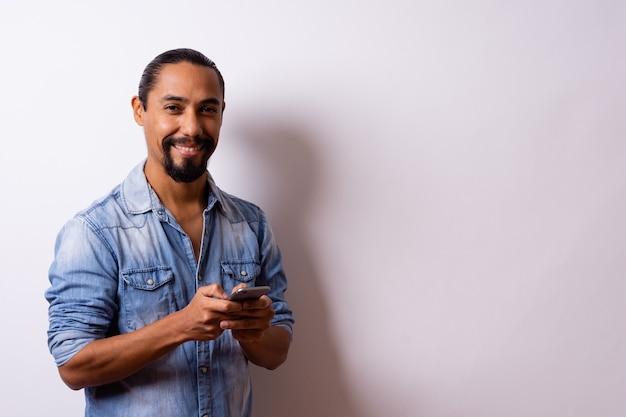 Homem latino olha para a câmera com grande atitude, segurando seu telefone celular para fazer uma compra em fundo branco. copie o espaço.