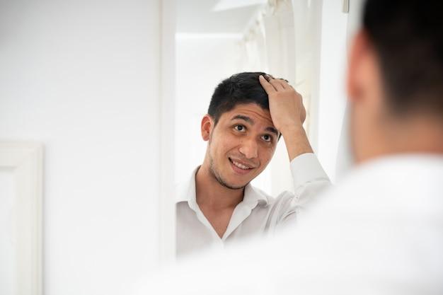 Homem latino penteando o cabelo na frente do espelho