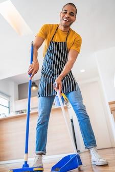 Homem latino que varre o assoalho de madeira com vassoura em casa.