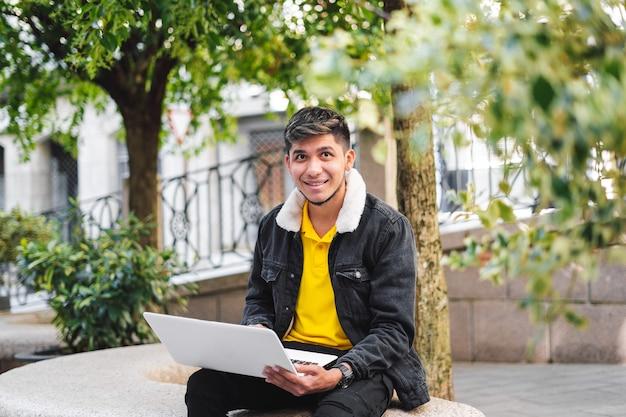 Homem latino sentado em um banco de pedra no parque com laptop olhando para a câmera