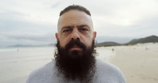 Homem latino sério com barba grande em uma praia, olhando para a câmera.