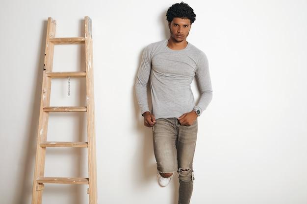 Homem latino sério usa manga comprida cinza em branco e posa perto de escada, isolado no branco