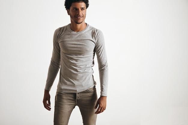 Homem latino sexy e bem ajustado, caminhando, usa manga de lã cinza sem rótulo em branco e jeans estressados, isolados no branco