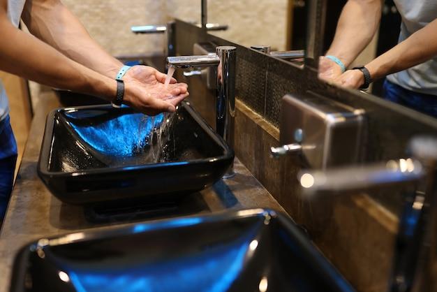 Homem lava a mão em local público com torneira com água. o banheiro tem pia preta elegante e torneira de metal.