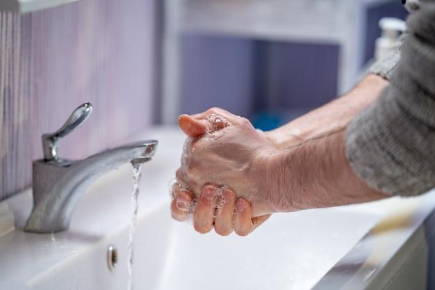 Homem lava as mãos com sabão em casa. proteção contra vírus de conceito. higiene das mãos.