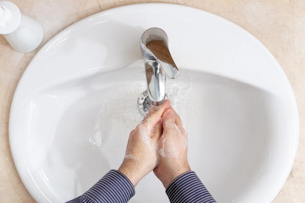 Homem lavando as mãos com água e sabão no banheiro. conceito de prevenção de coronavírus
