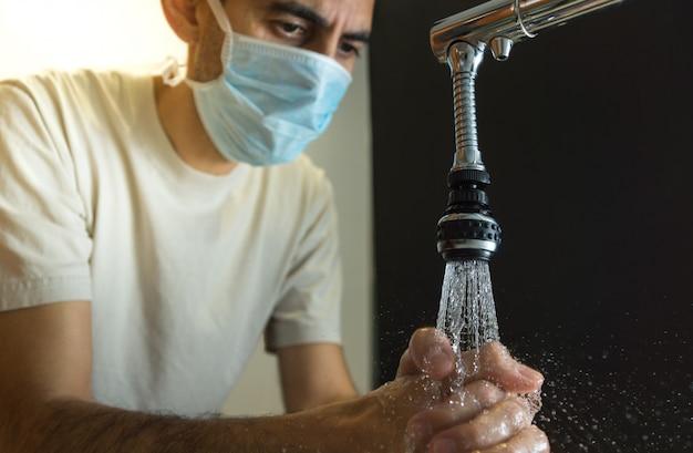 Homem lavando as mãos com máscara