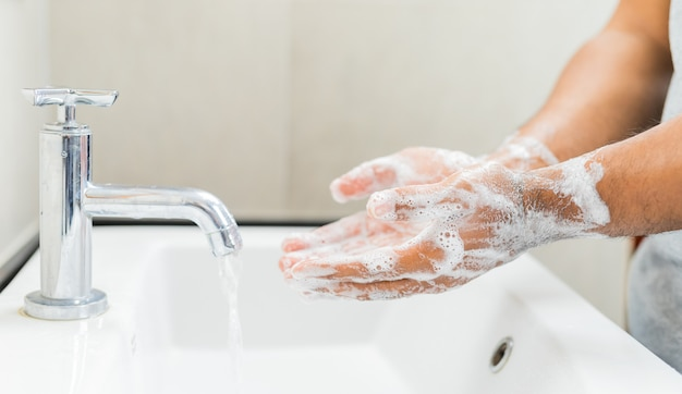 Homem lavando as mãos com sabão.