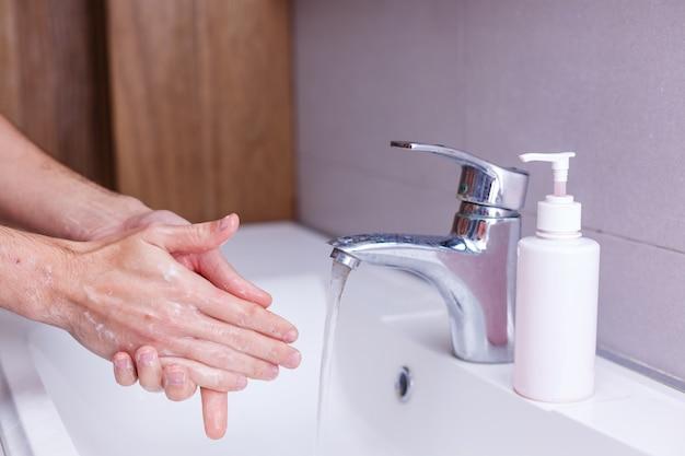 Homem lavando as mãos em água corrente, em um banheiro público.