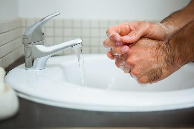 Homem lavando as mãos no lavatório