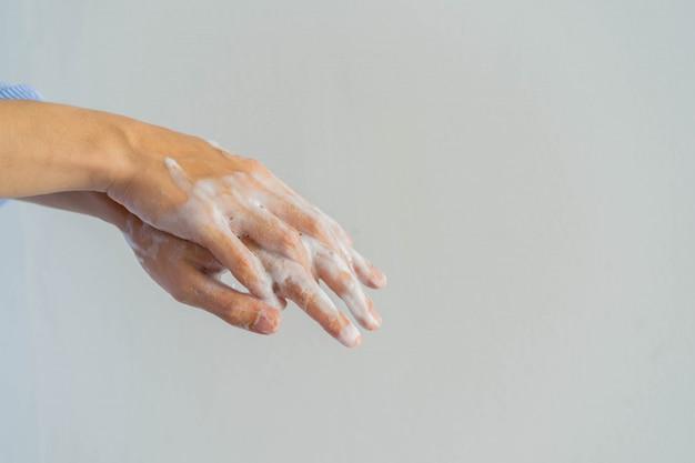 Homem lavando e esfregando a mão para limpar sabão