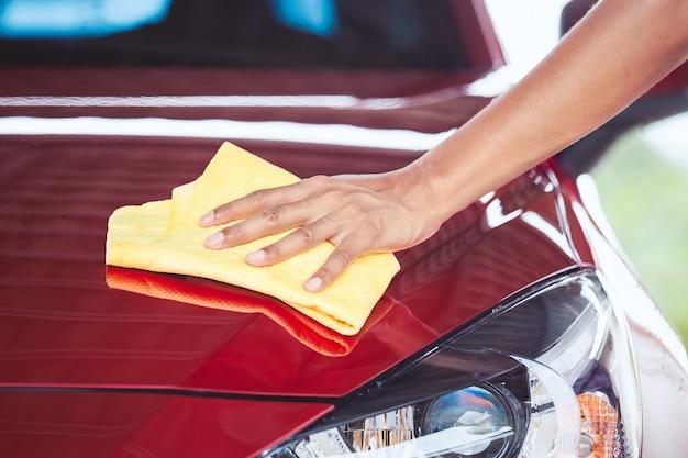 Homem lavando e limpando o carro vermelho com pano de microfibra