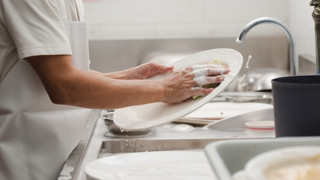 Homem lavando louça na pia de restaurante