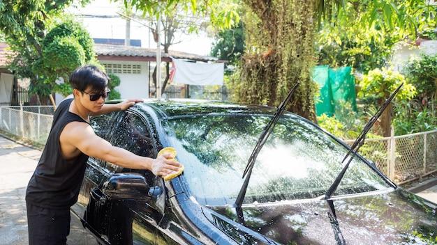 Homem lavando o carro preto.