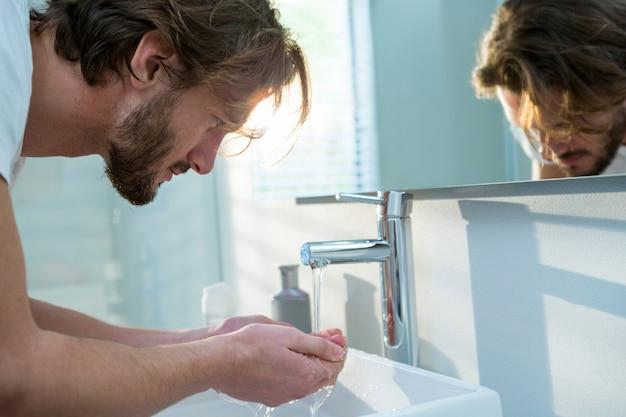 Homem lavando o rosto com água no banheiro