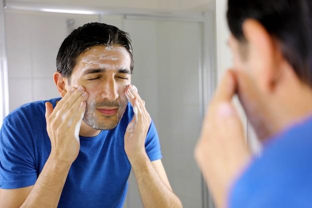 Homem lavando o rosto com sabonete de limpeza facial no banheiro