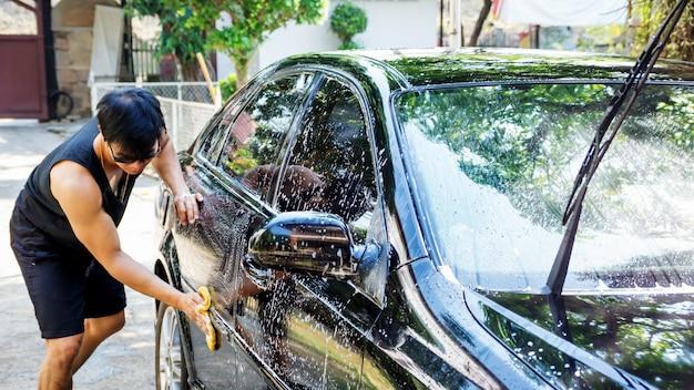 Homem lavando um carro preto.