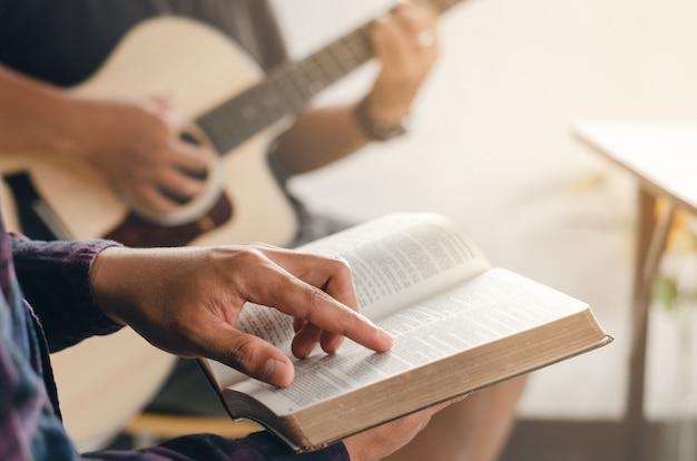 Homem lê a bíblia enquanto seus amigos tocam violão de perto