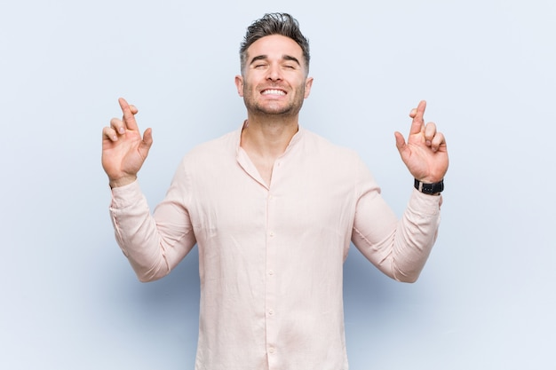Homem legal considerável novo que cruza os dedos para ter sorte