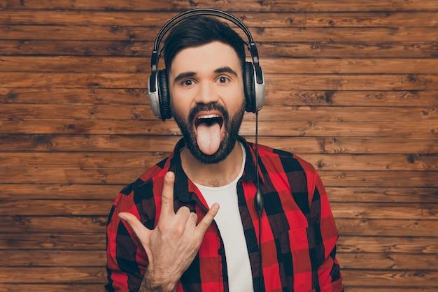 Homem legal em fones de ouvido mostrando gesto de pedra e língua
