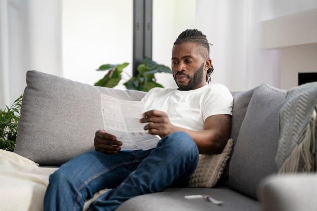 Homem lendo as instruções para um teste cobiçoso em casa