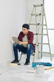 Homem lendo instruções antes de pintar
