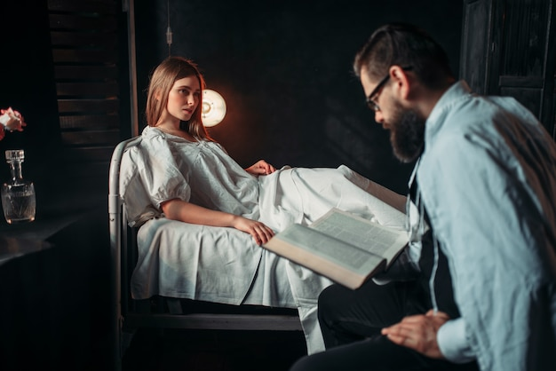 Homem lendo livro contra mulher doente na cama do hospital
