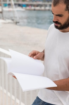 Homem lendo livro de miçangas ao ar livre