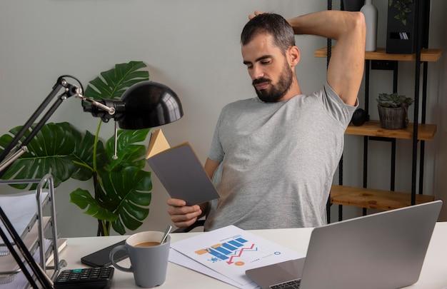 Homem lendo livro enquanto trabalha em casa