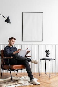 Homem lendo na sala de estar com moldura em branco