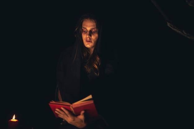 Homem lendo um livro de feitiços no escuro