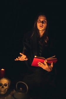 Homem lendo um livro de feitiços vermelho no escuro e olhando para a câmera