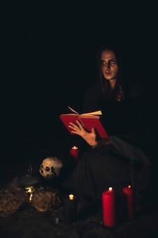Homem lendo um livro de feitiços vermelho no escuro