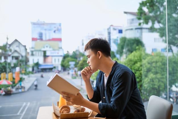 Homem lendo um livro em uma cafeteria