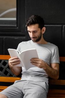 Homem lendo um livro interessante em um banco