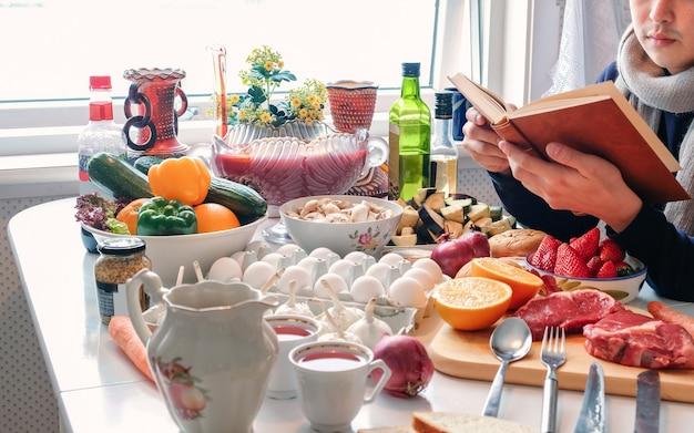 Homem lendo um livro na mesa de jantar com vários ingredientes de cozinha para a celebração do festival na temporada de inverno