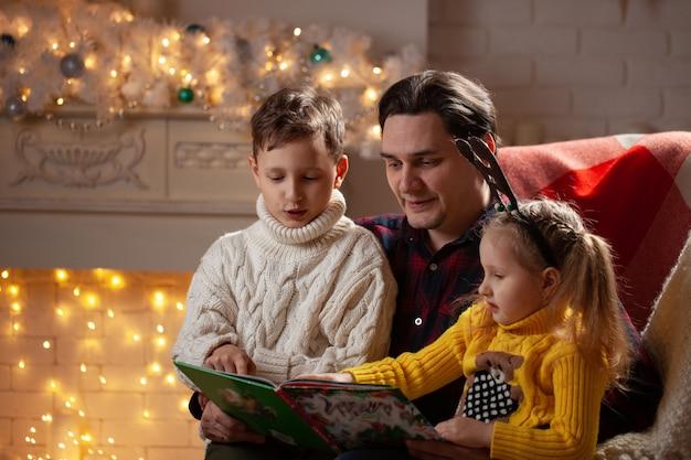 Homem lendo um livro para um menino e uma menina
