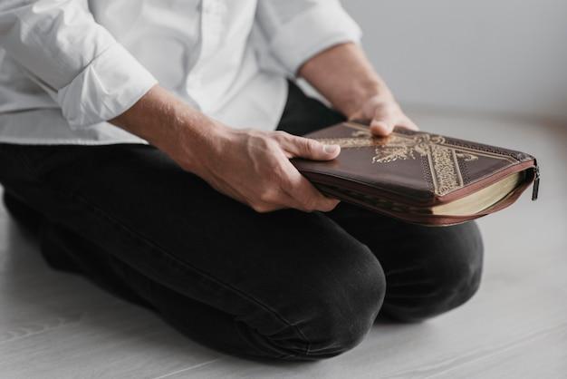 Homem lendo um livro sagrado em casa