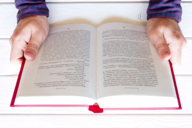 Homem lendo um livro sobre um foco seletivo de fundo branco de madeira