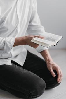 Homem lendo um pequeno livro sagrado