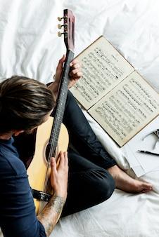 Homem lendo uma nota musical e tocando uma guitarra