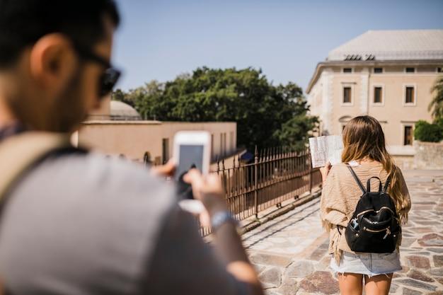 Homem, levando, fotografia, de, mulher olha, em, mapa, ficar, ligado, rua